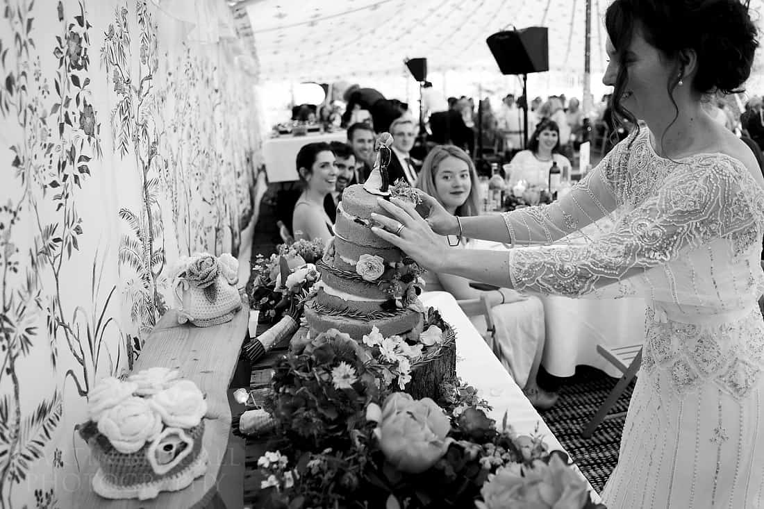 Bride steadies a toppling wedding cake