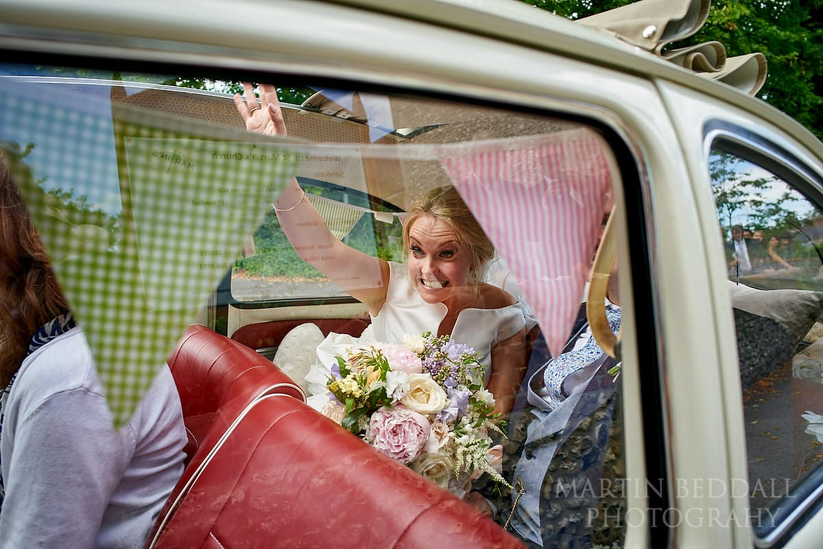 Bride waves from the wedding car