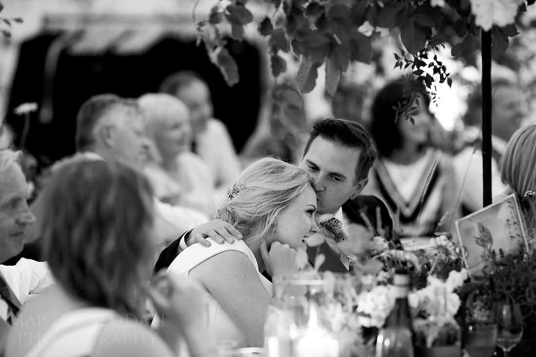groom kisses bride during speeches
