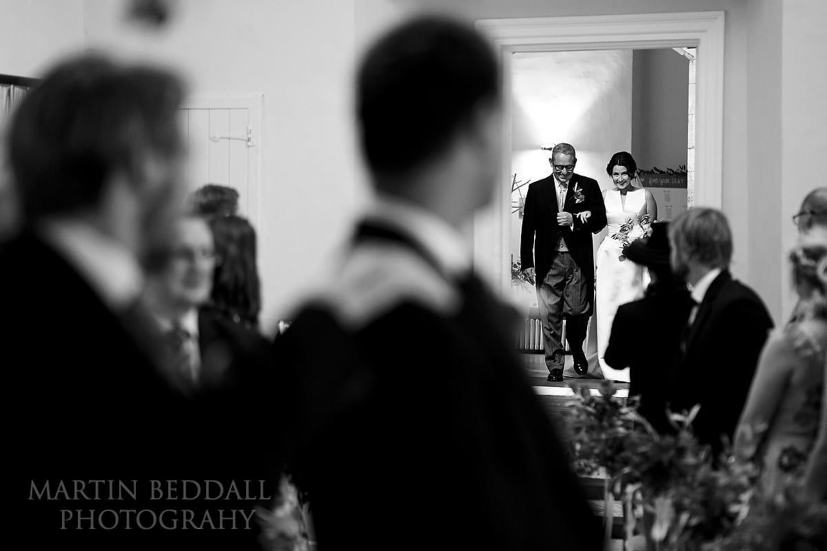 Bride enters the ceremony room at Farnham Castle