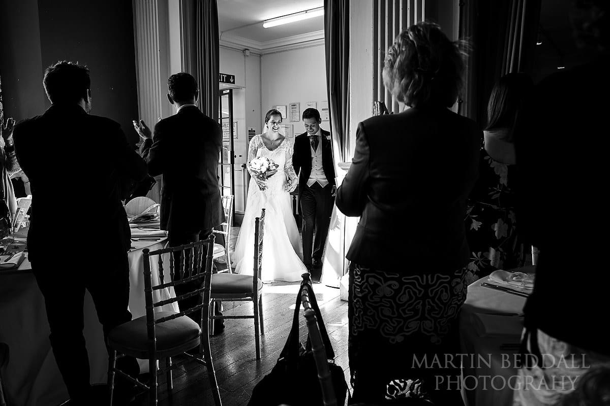 Bride and groom enter into dinner at Slindon College