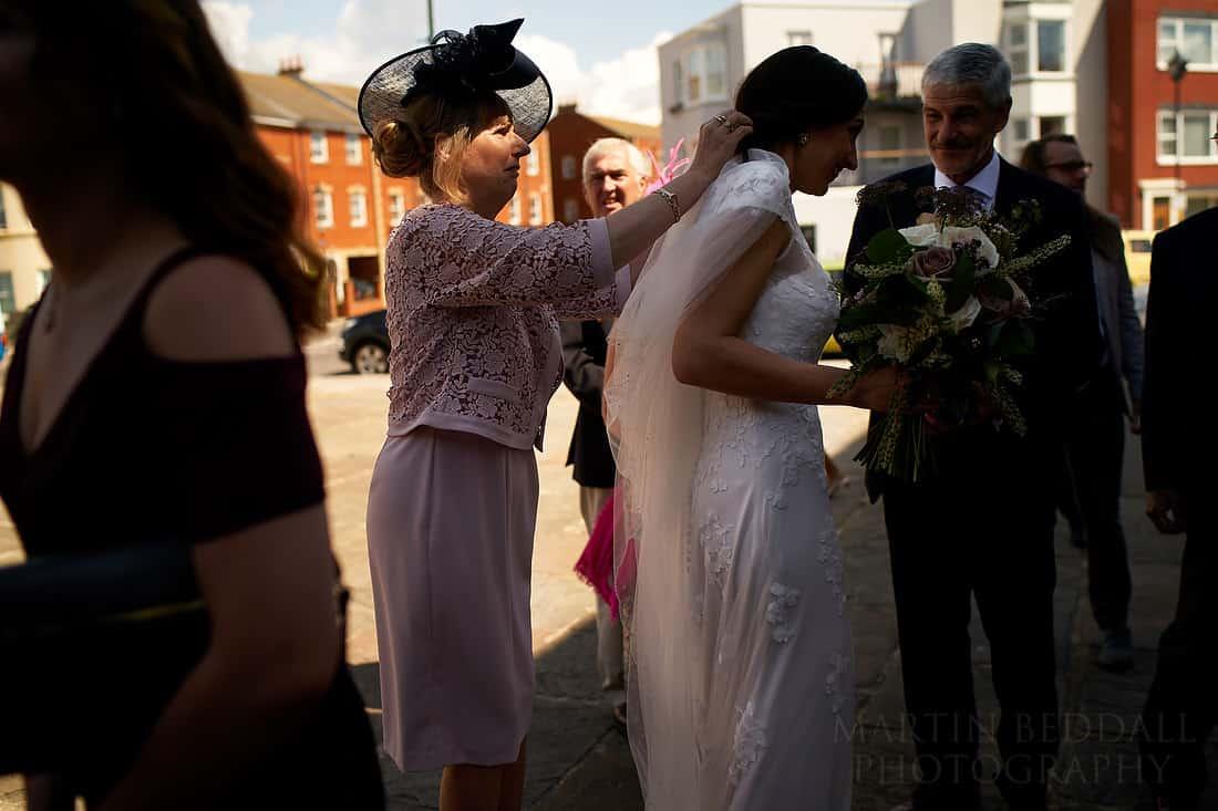 Mother adjusts the bride's veil