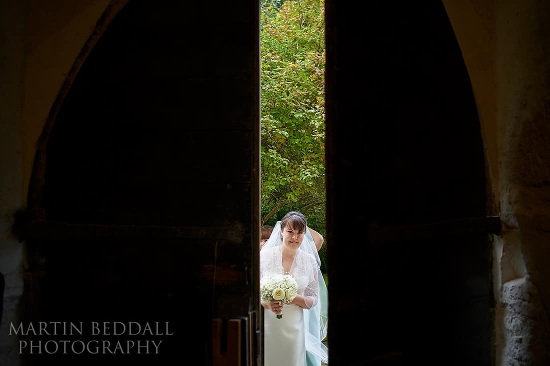 Bride sneaking a peek into the church