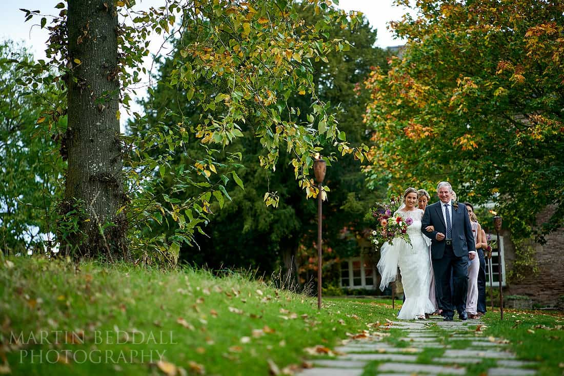 Bride walks with her father to the wedding ceremony