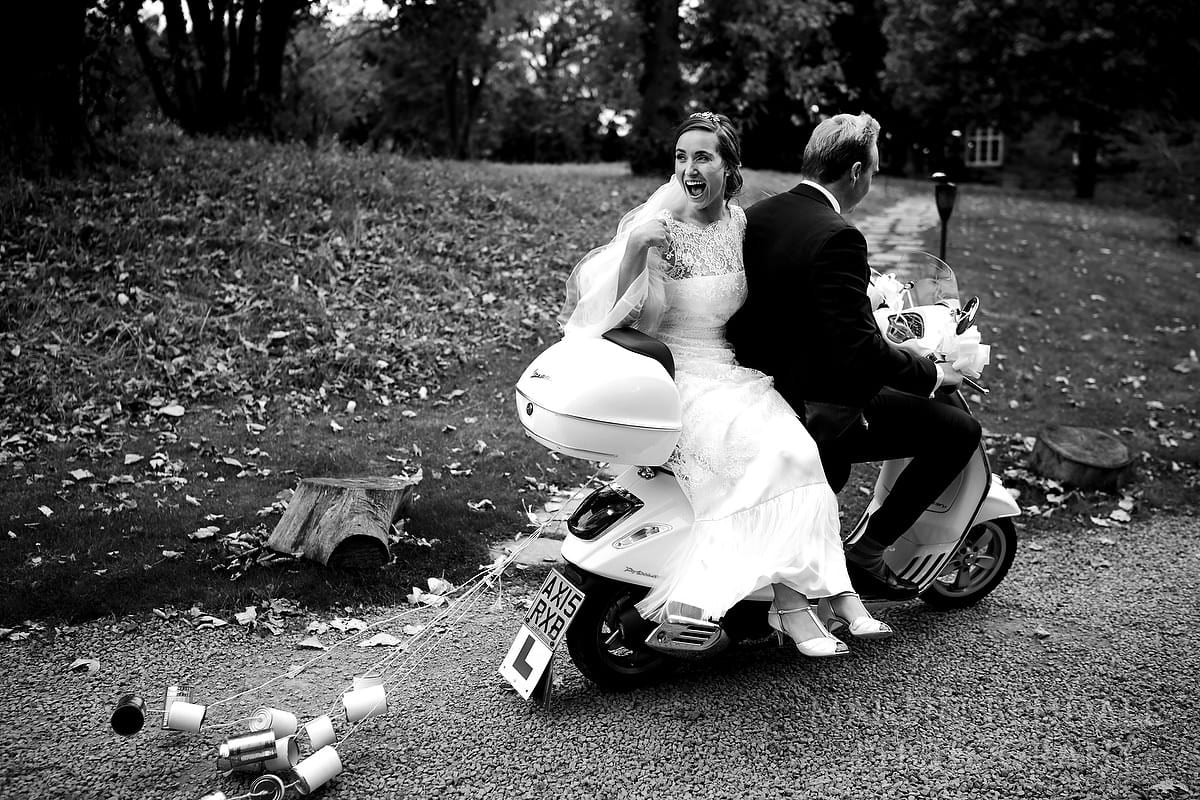 Groom and bride drive off on their Vespa