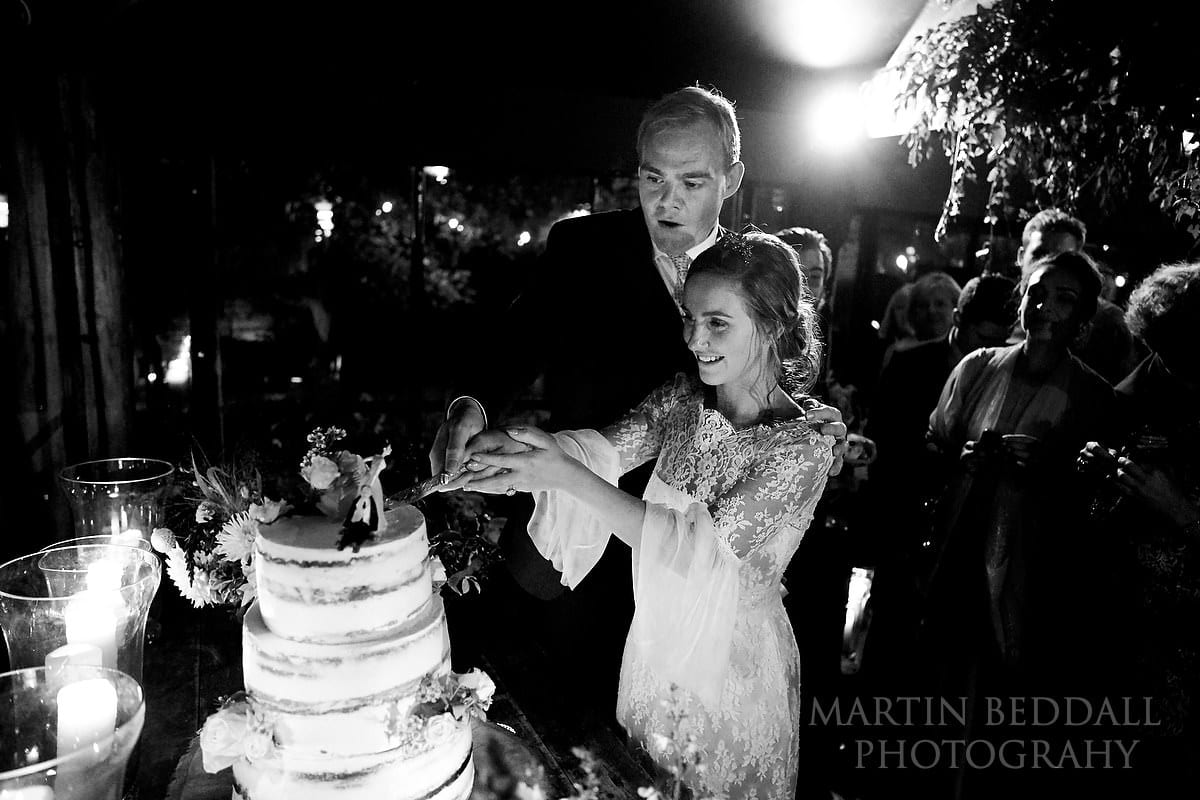 Cutting the wedding cake at Dewsall Court wedding