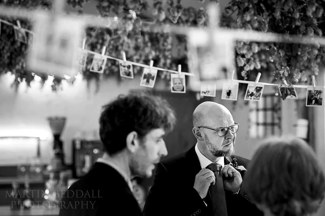 Groom adjusting his tie in the Pheasantry at Gate Street Barn