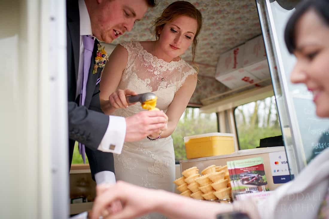Bride and groom handing out the ice cream from the van