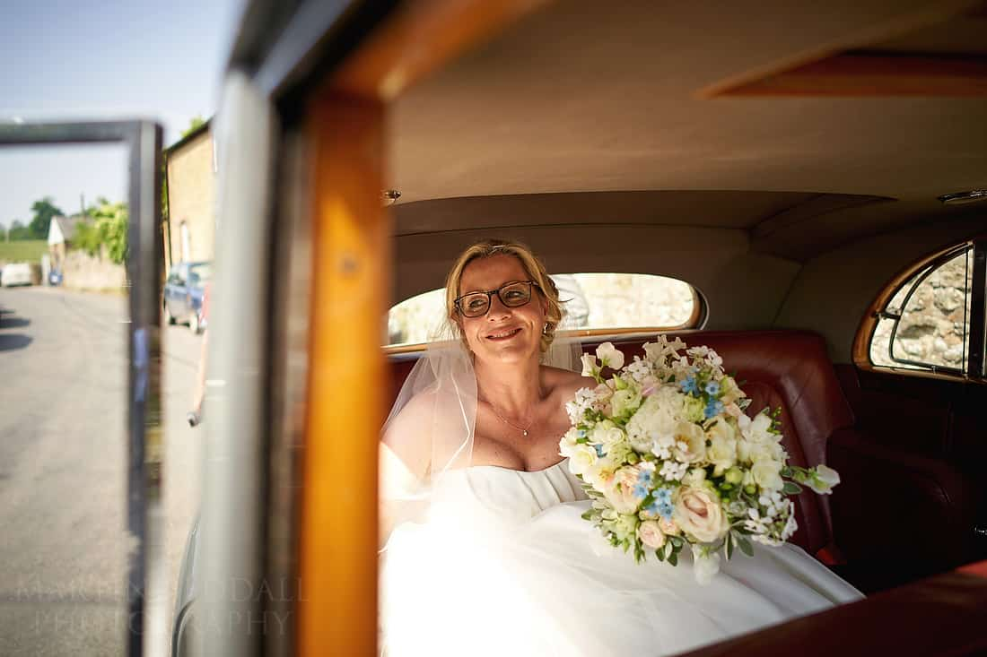 Smiling bride in the wedding car