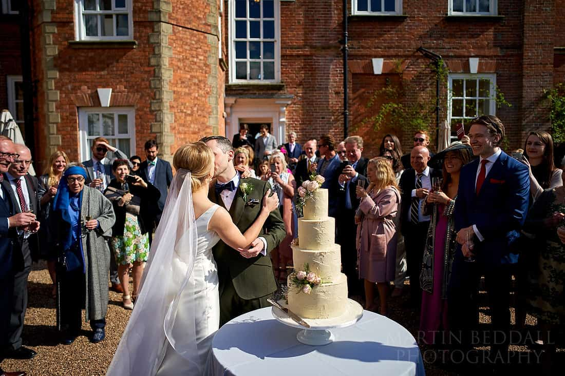 Kiss after cutting the wedding cake outside