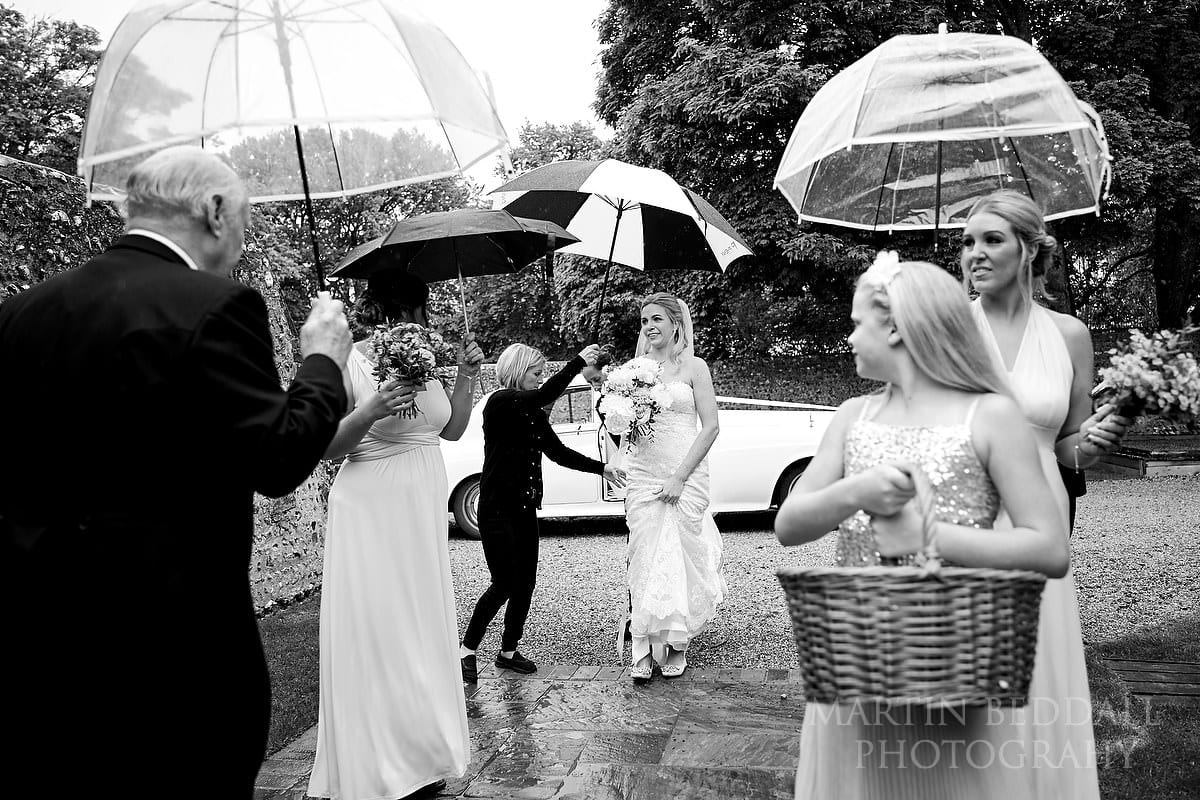 Bride arrives for a Wet wedding at Cissbury Barns