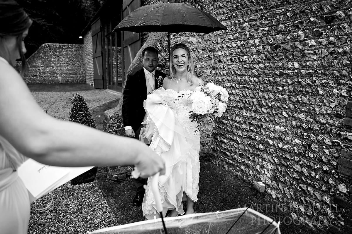Bride shelters from the rain at Wet wedding at Cissbury Barns