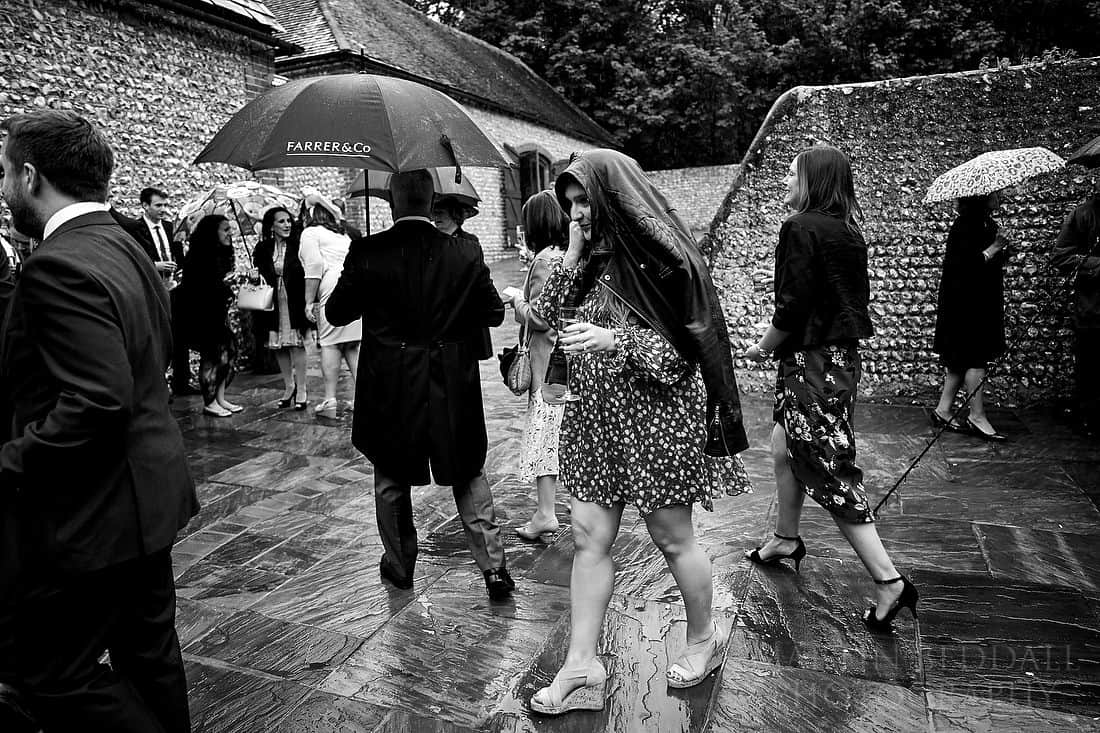 Wedding guests assemble in the rain for the confetti