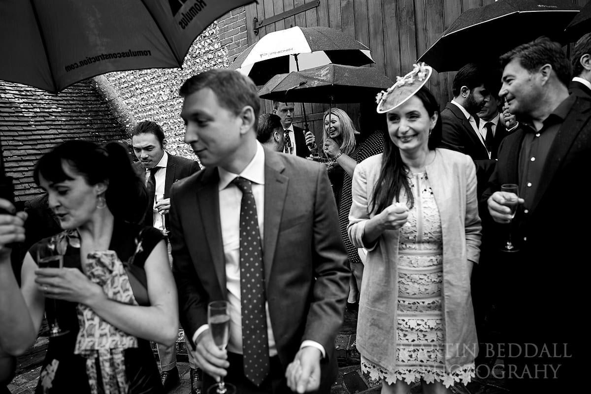 Wedding guests wait in the rain at Wet wedding at Cissbury Barns