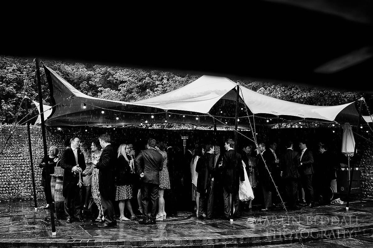 Guests shelter from the rain at Wet wedding at Cissbury Barns