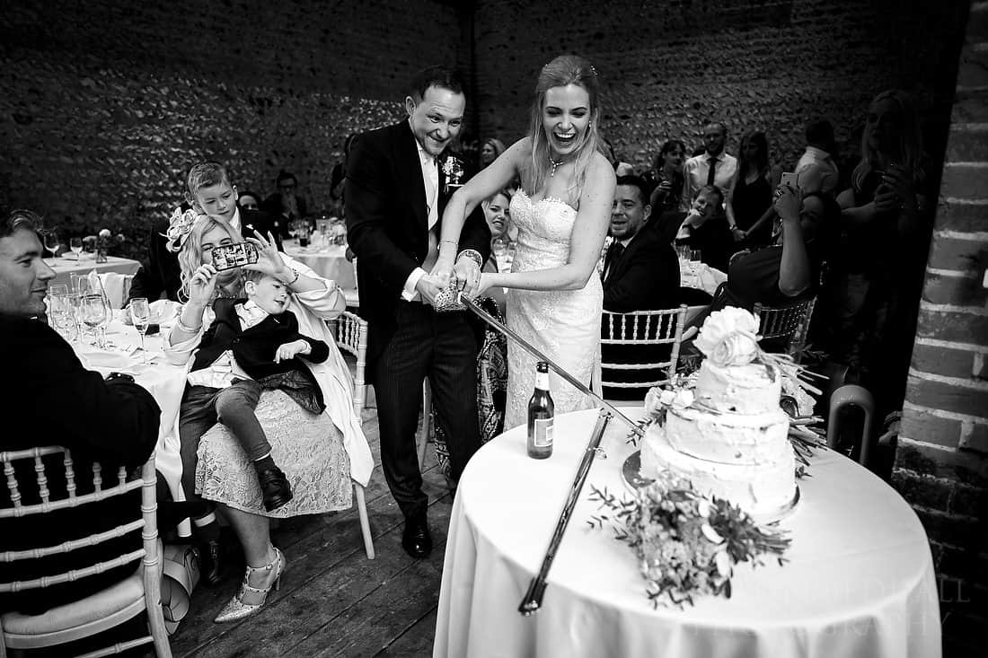 Cutting the wedding cake with an Army sword