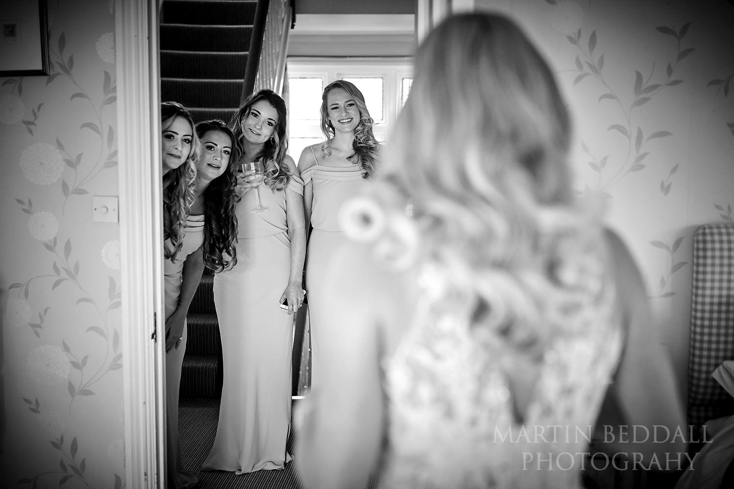 Bridesmaids see the bride in her wedding dress