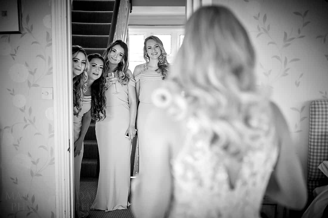 Bridesmaids gather to see the wedding dress