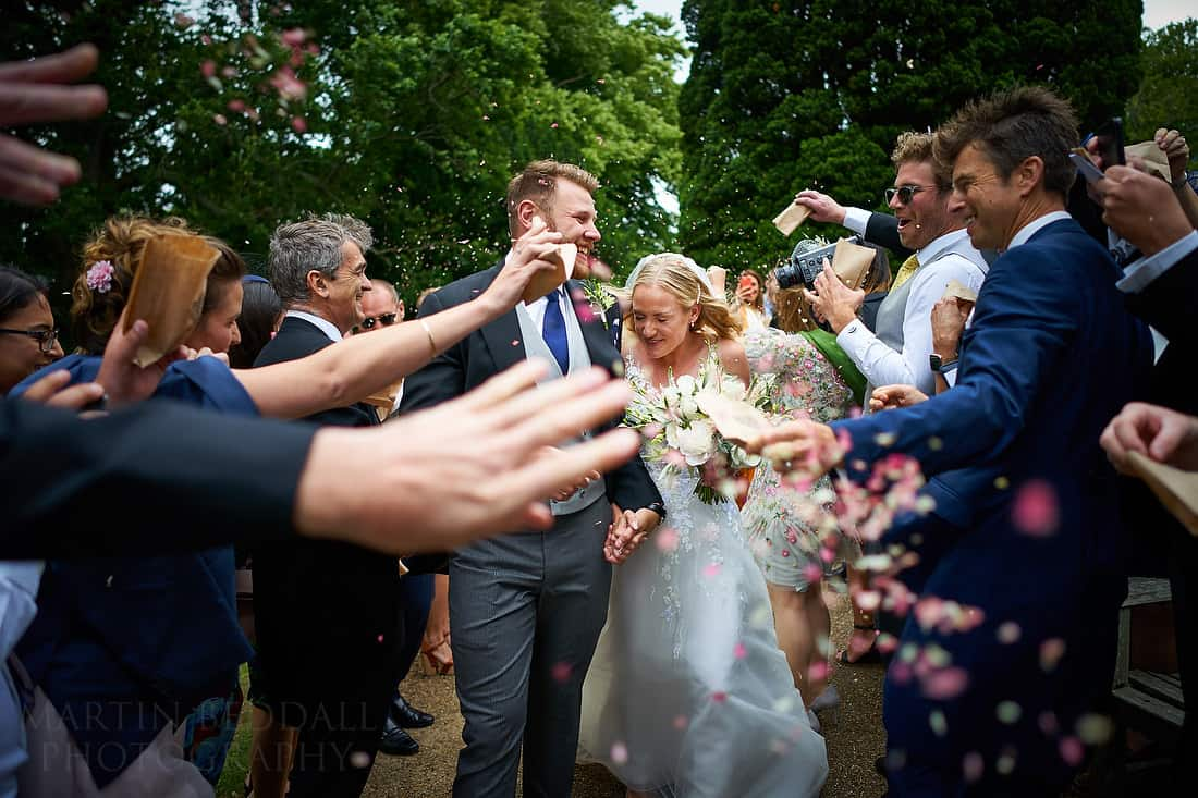 bride and groom run the confetti gauntlet