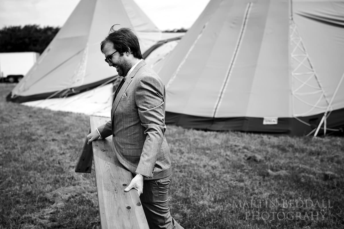 Groom sets up the benches foe the open air wedding ceremony at The Party Field