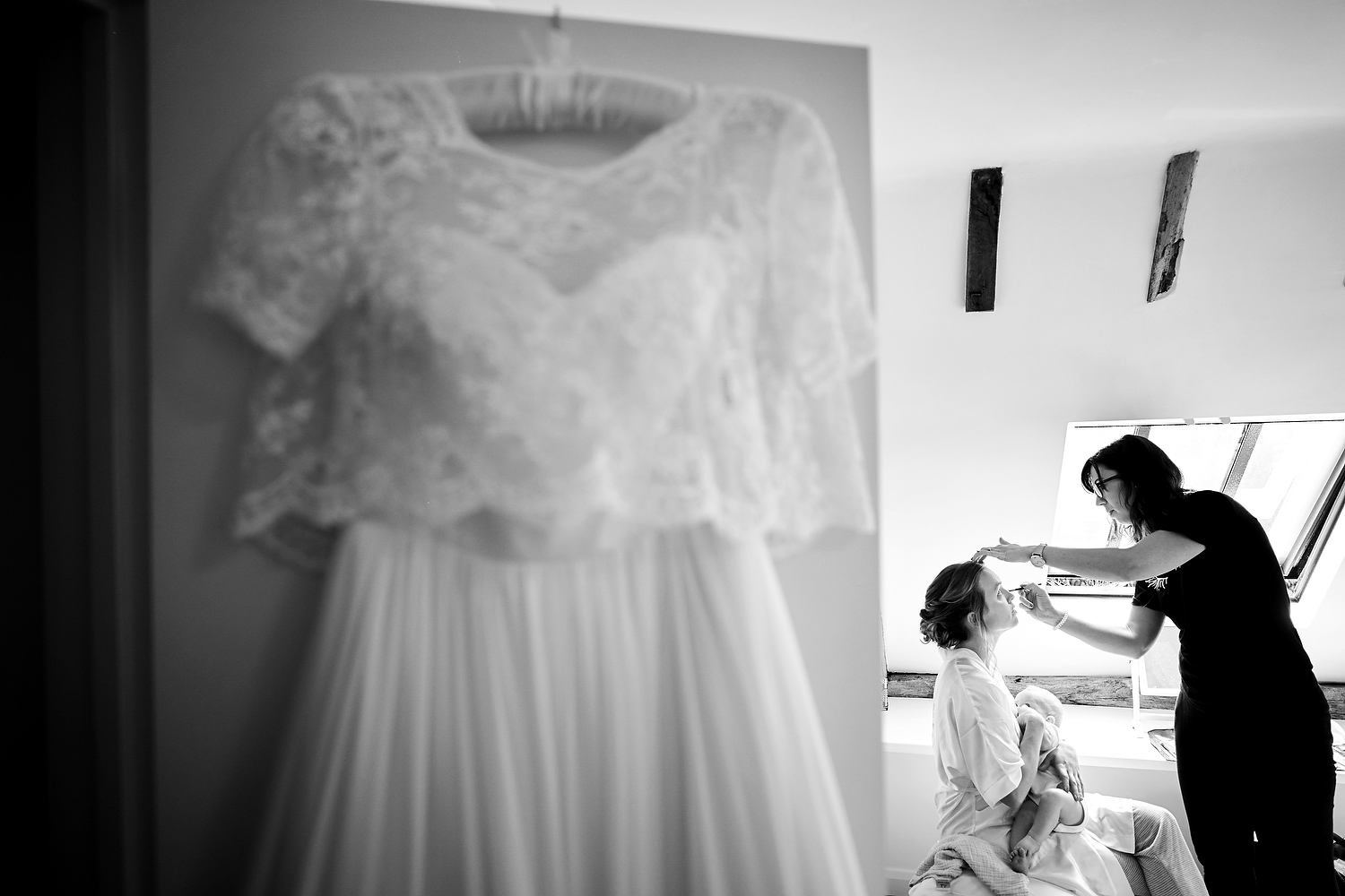 Bride breastfeeds her baby as she gets ready