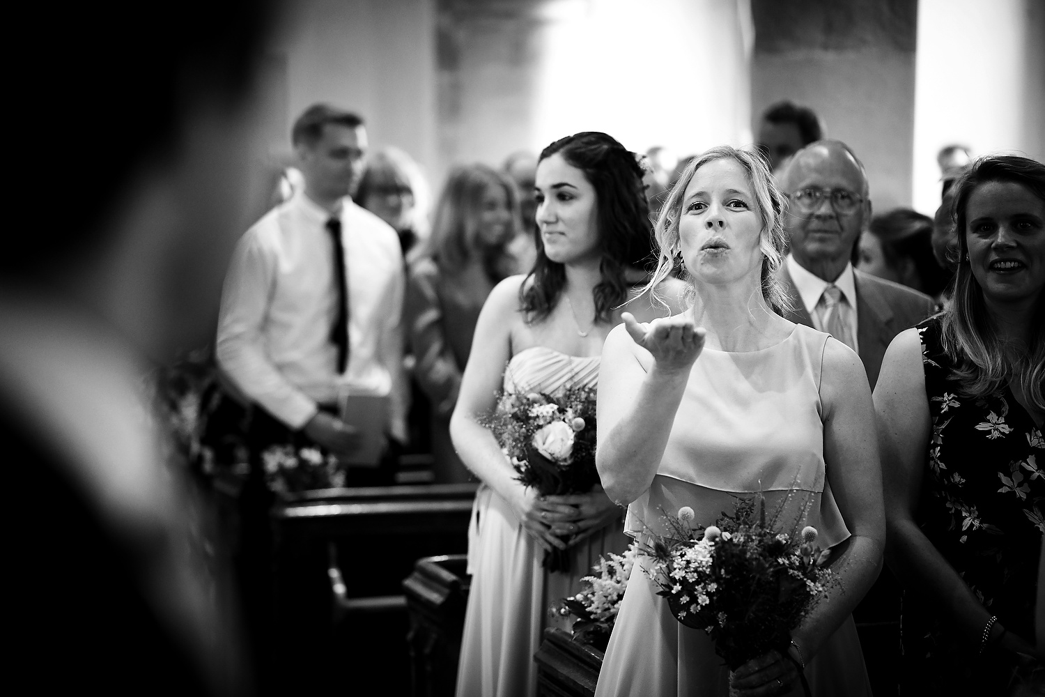 Blowing the groom a kiss at Sussex village wedding