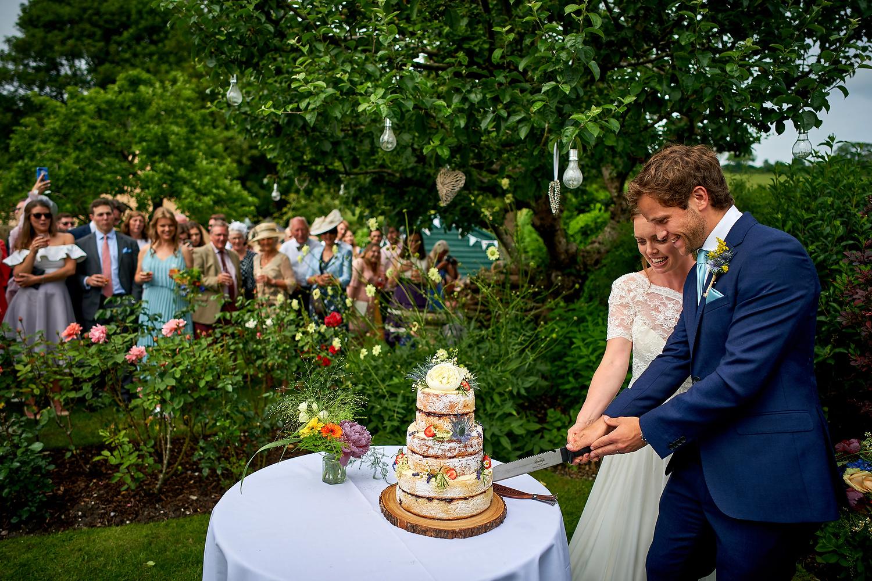 Cutting the wedding cake at Sussex village wedding