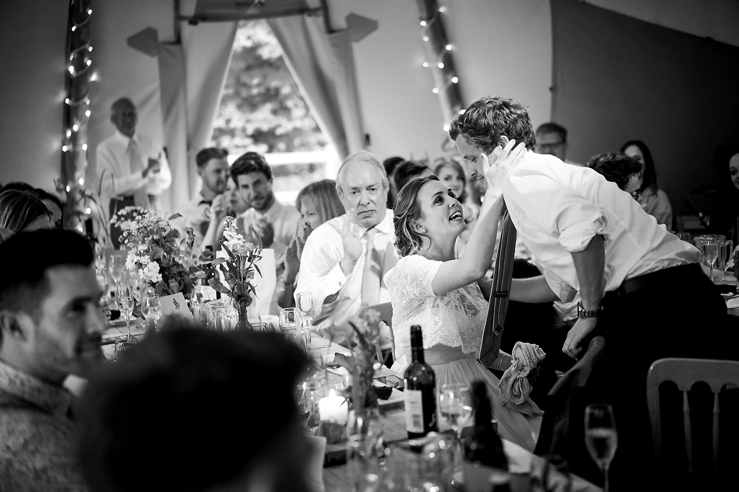 Bride kisses the groom after his speech at Sussex village wedding wedding