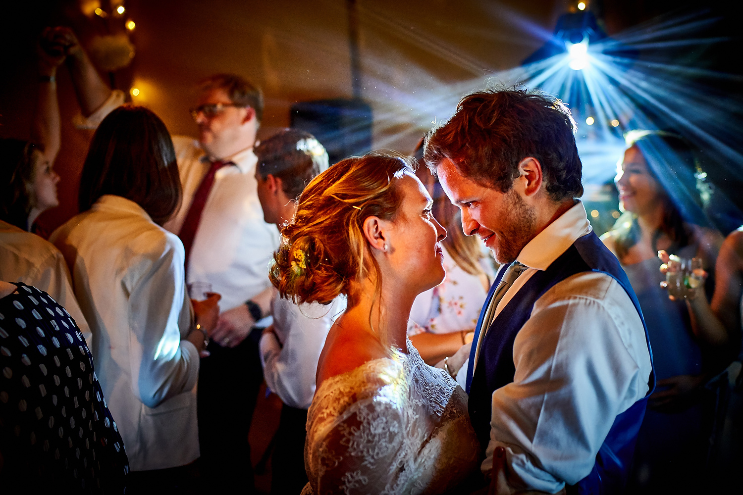 Bride and groom reflect on the dance floor at Sussex village wedding