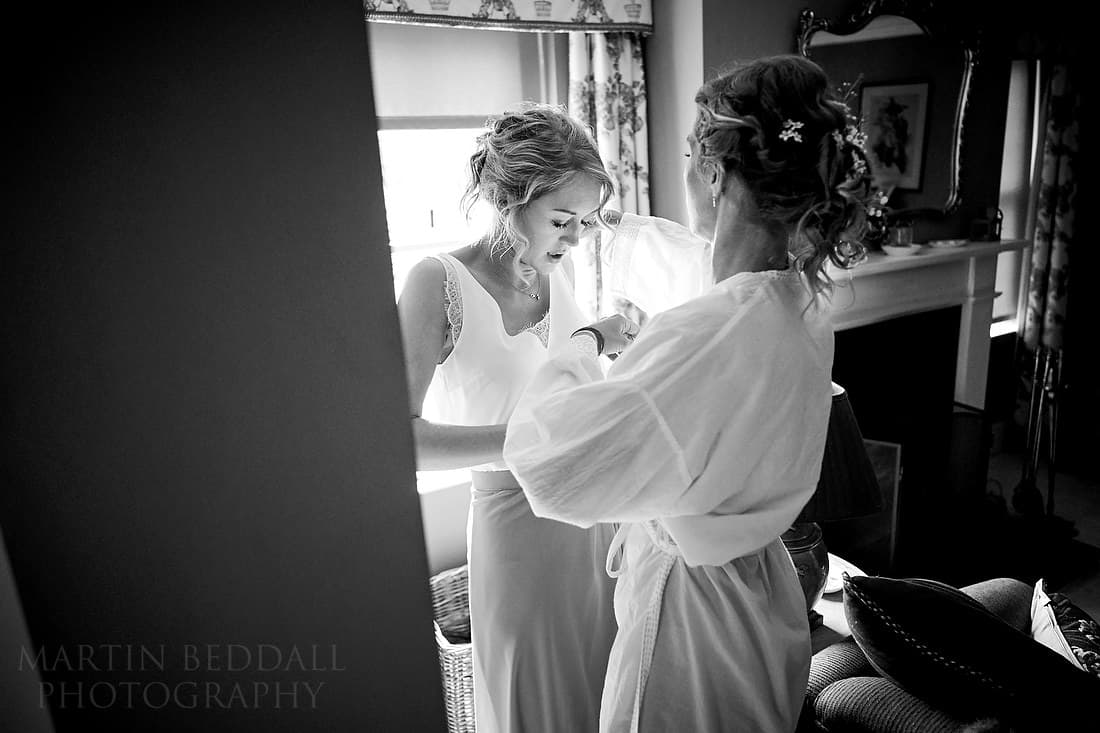 bride helps a bridesmaid get dressed