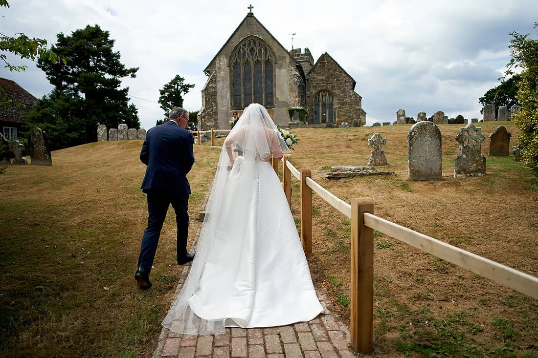 Bride and her father walk up to the church