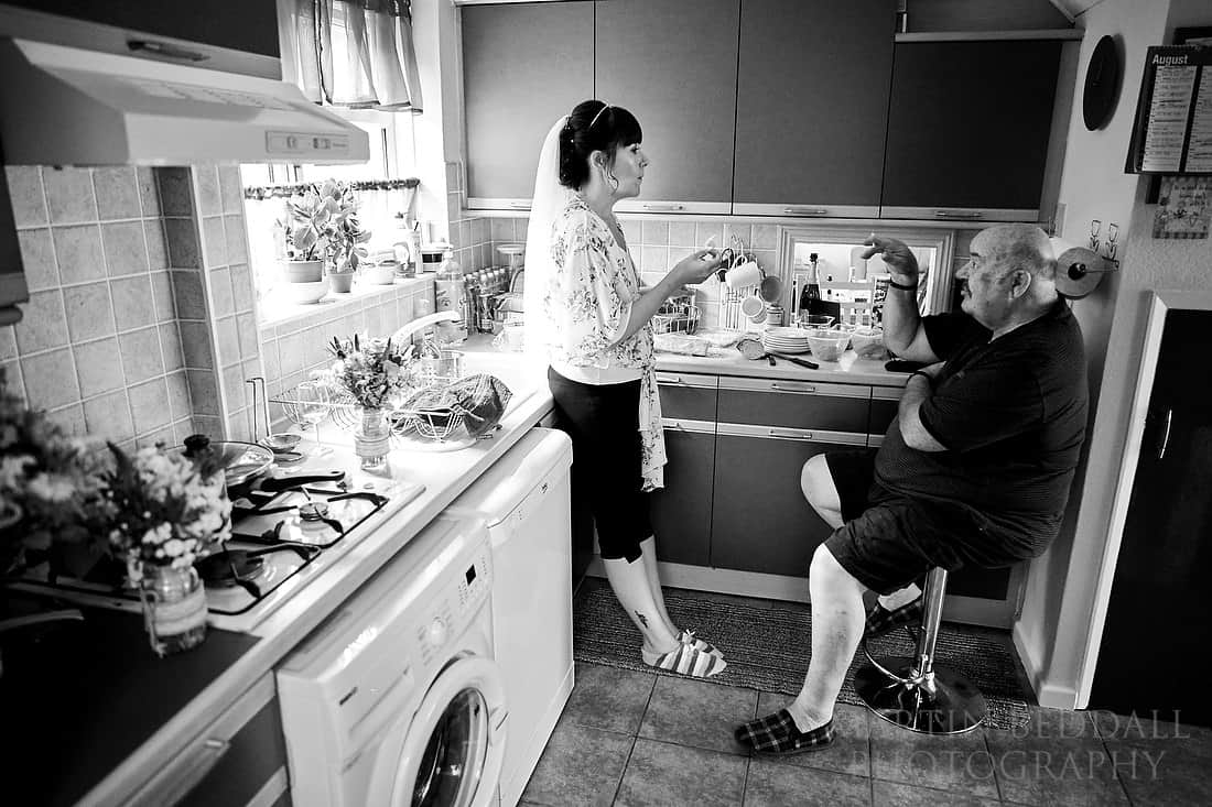 Bride chats with her father in the kitchen