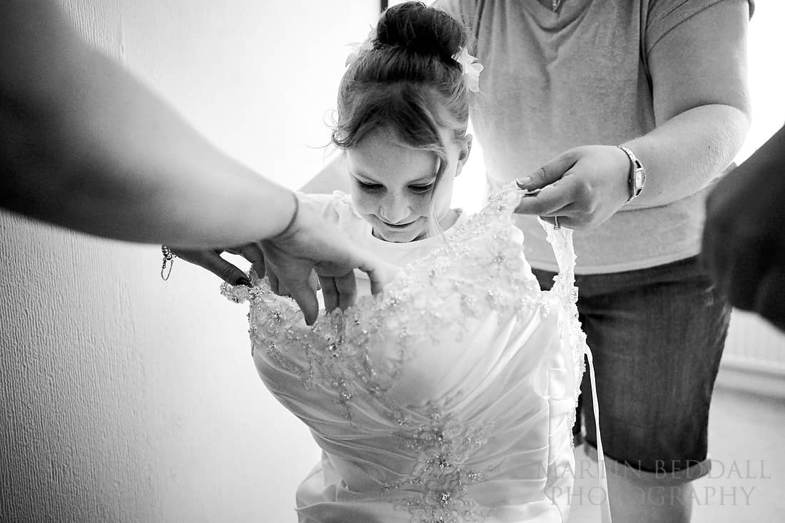 Flower girl tries on the bride's wedding dress