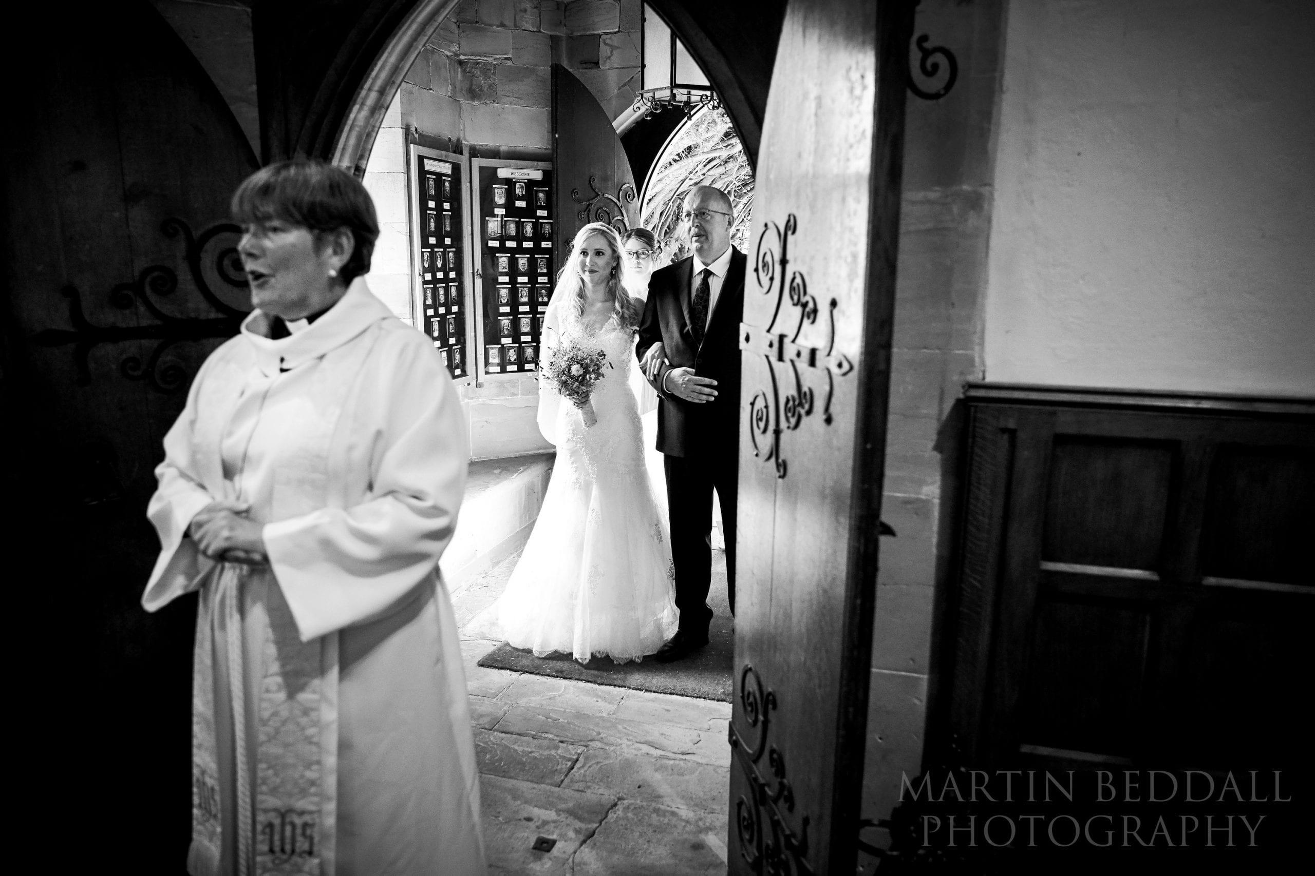 Bride and her father wait to enter Warnham church wedding