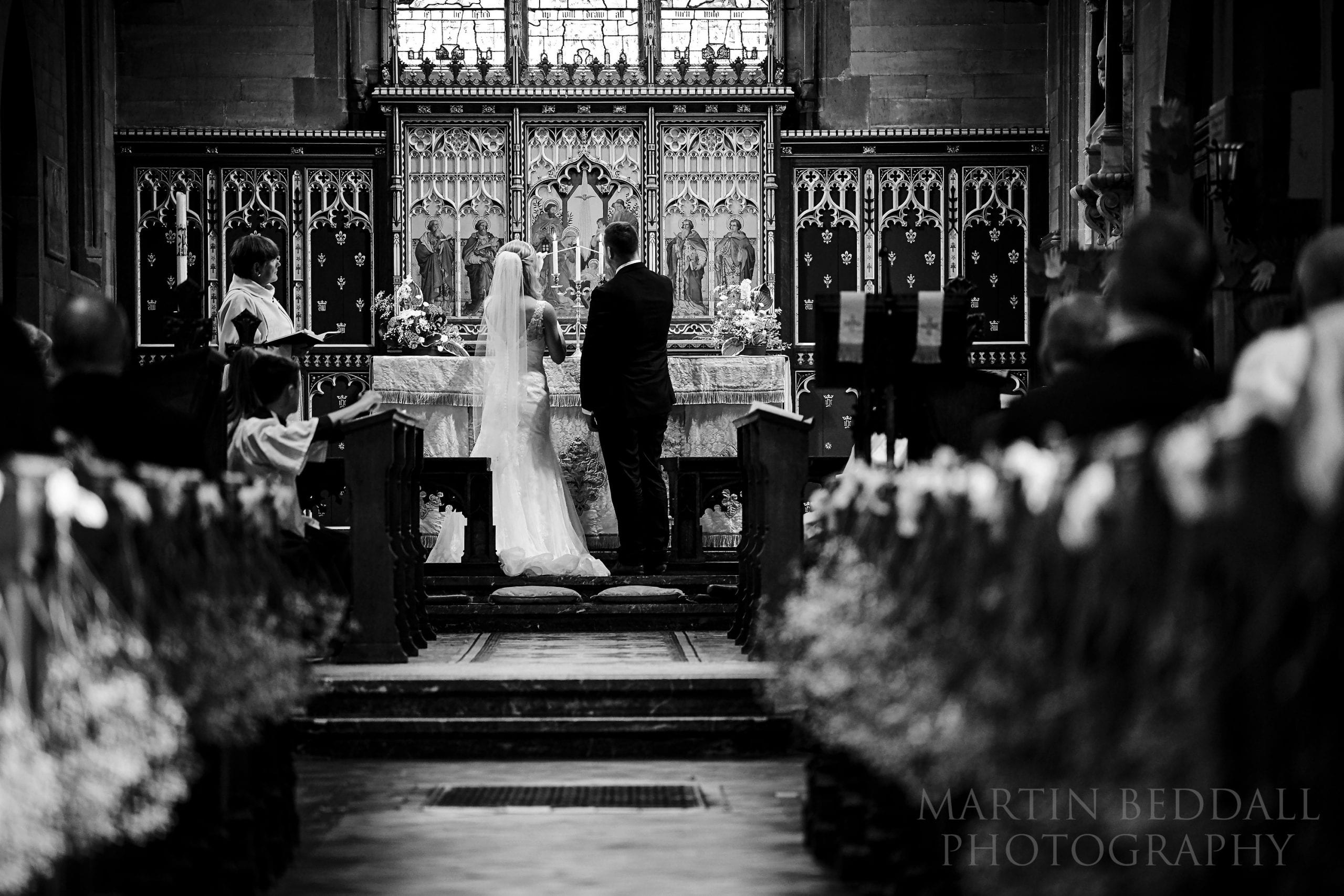 Bride and groom light candles on the altar of Warnham church