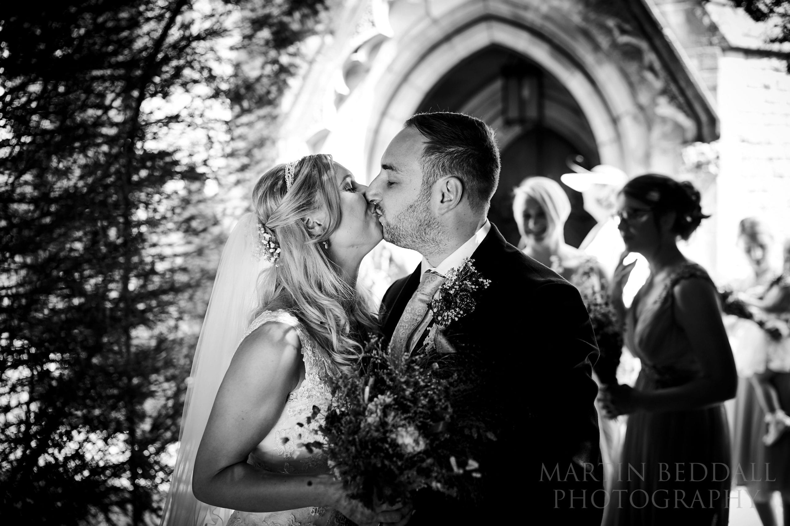Bride and groom kiss outside the church