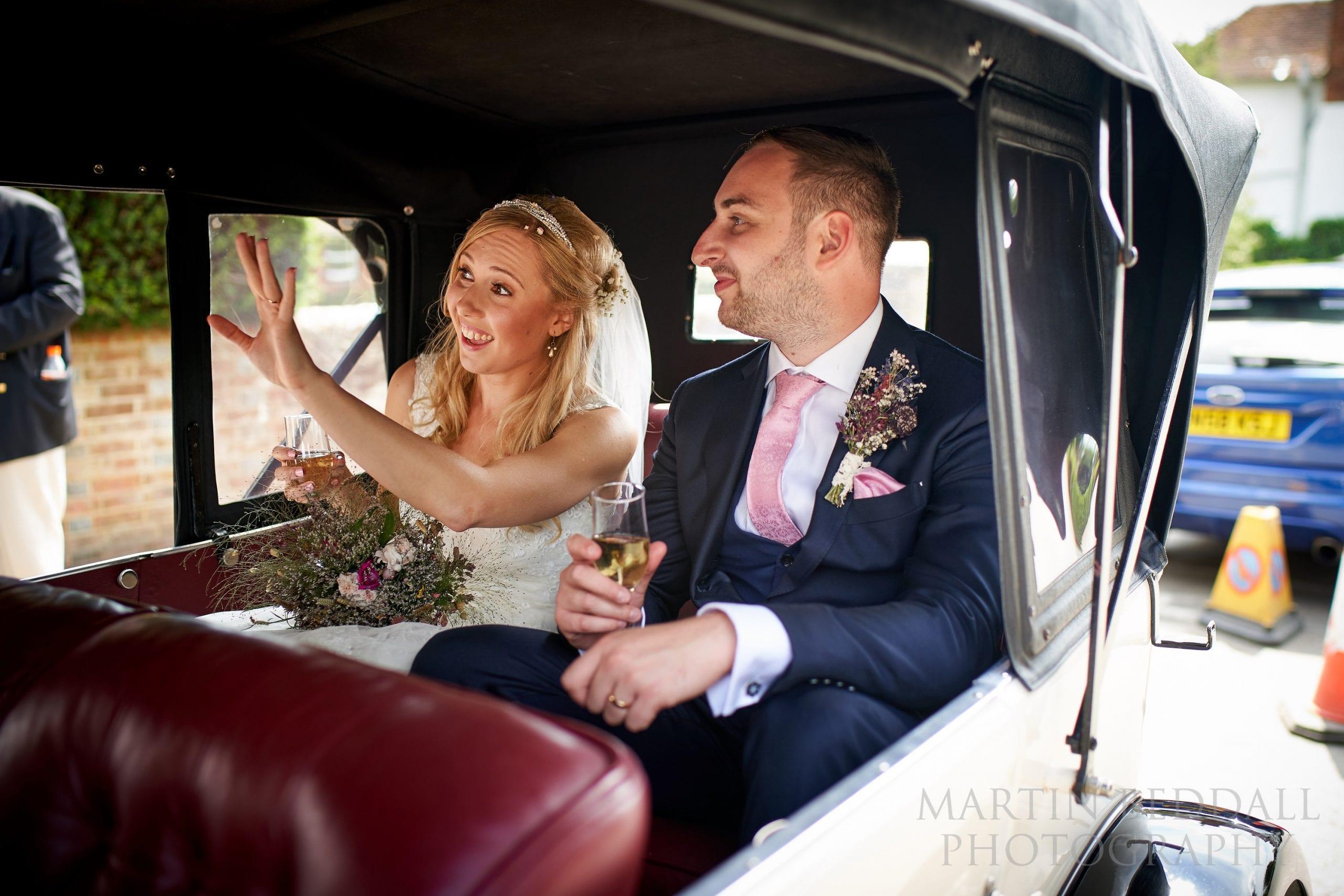 Bride and groom in the vintage wedding car