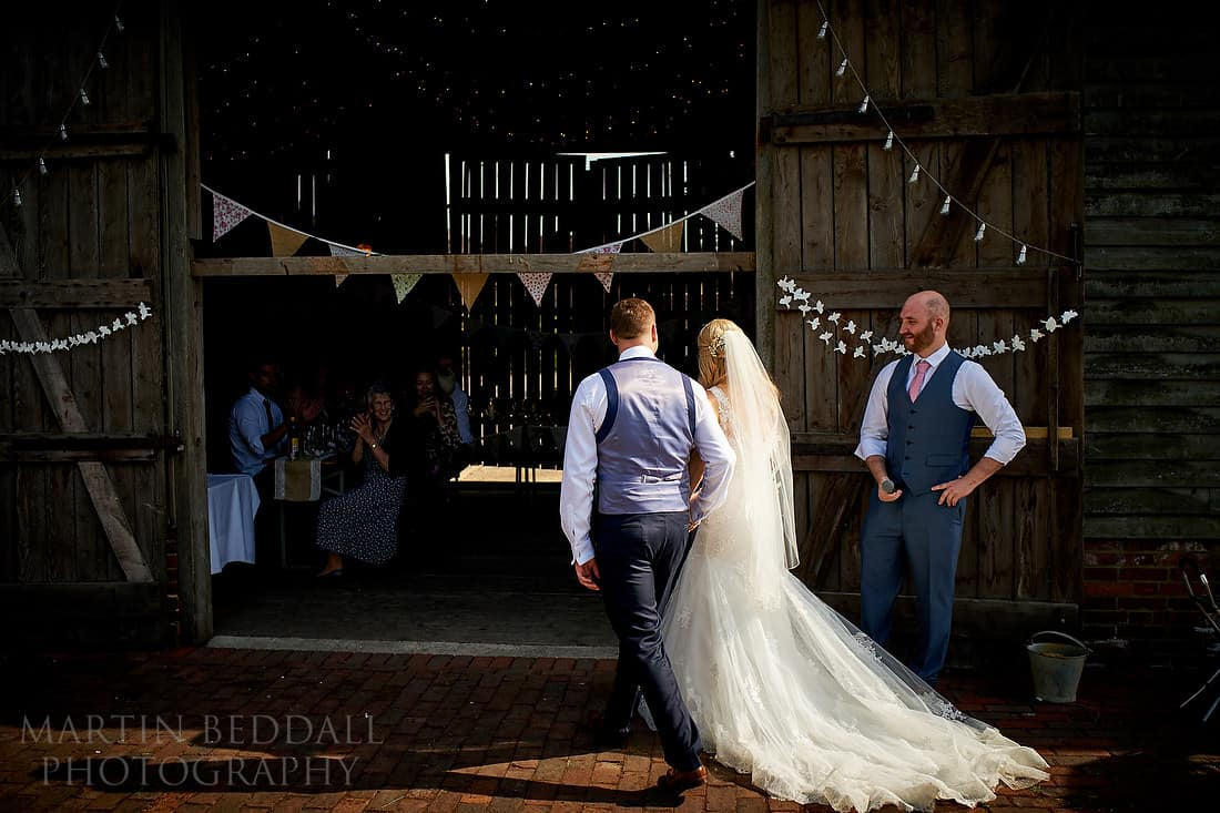Bride and groom enter the barn for dinner