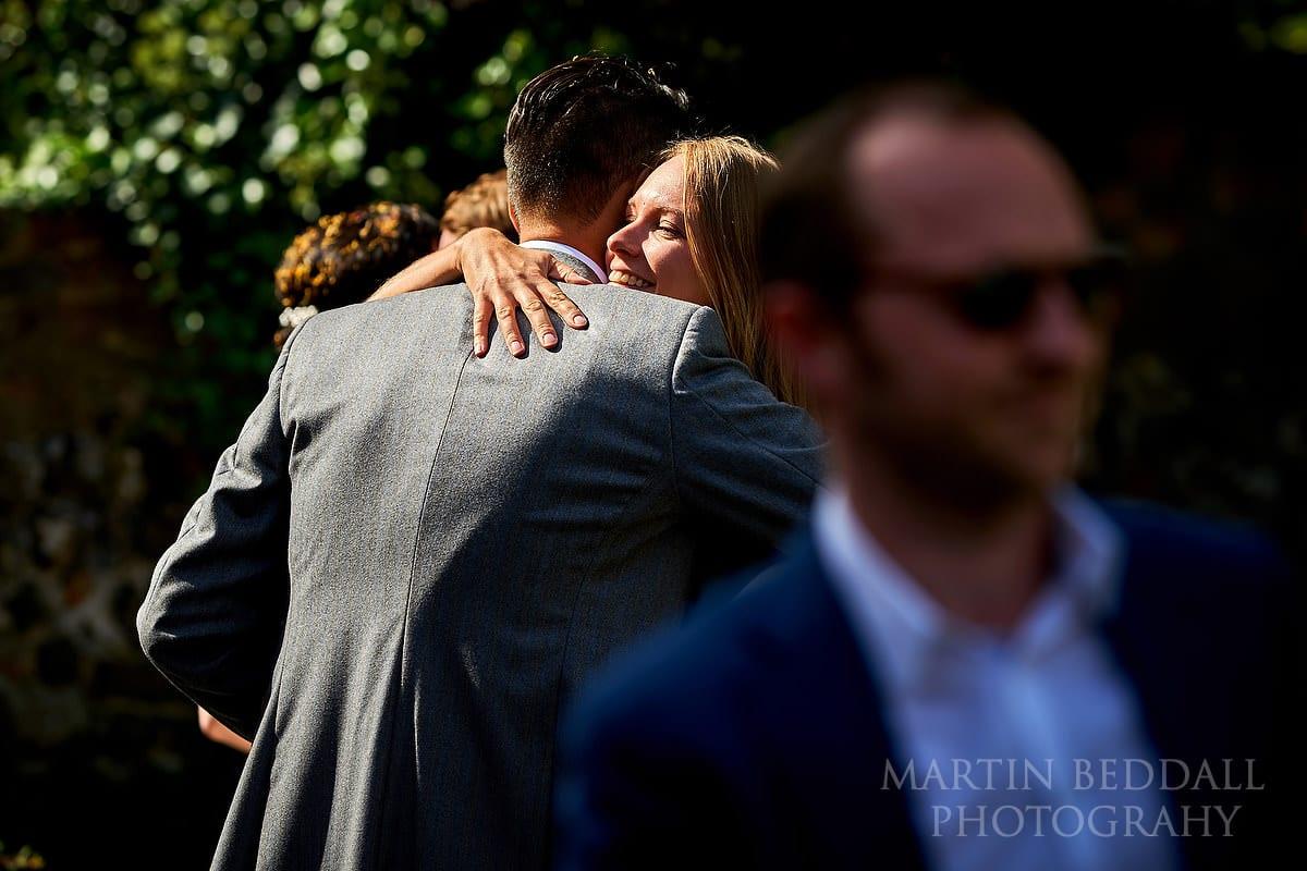 Hug for the groom in the September sunshine