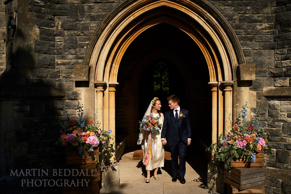Bride and groom emerge from the church into the sunshine