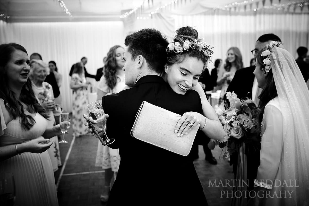 Bride's sister hugs the groom