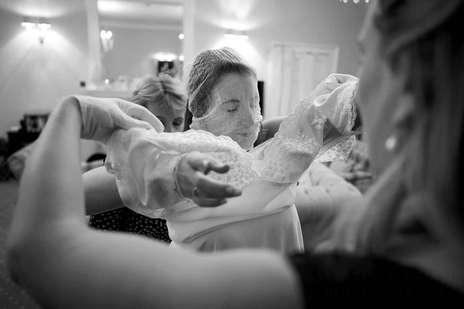 bride gets into her wedding dress