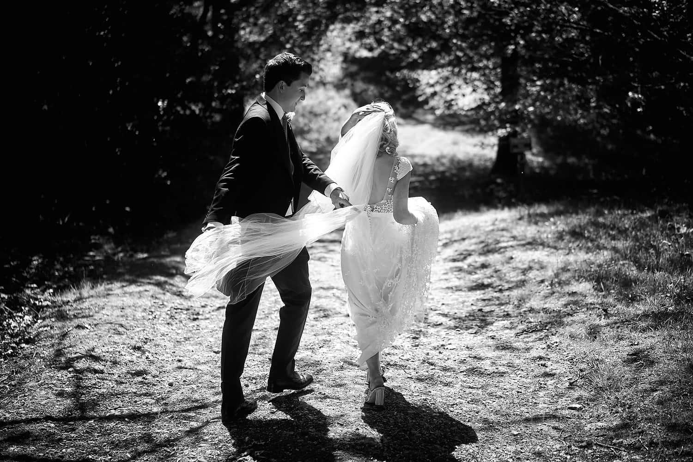 Groom adjusts bride's veil in the wind