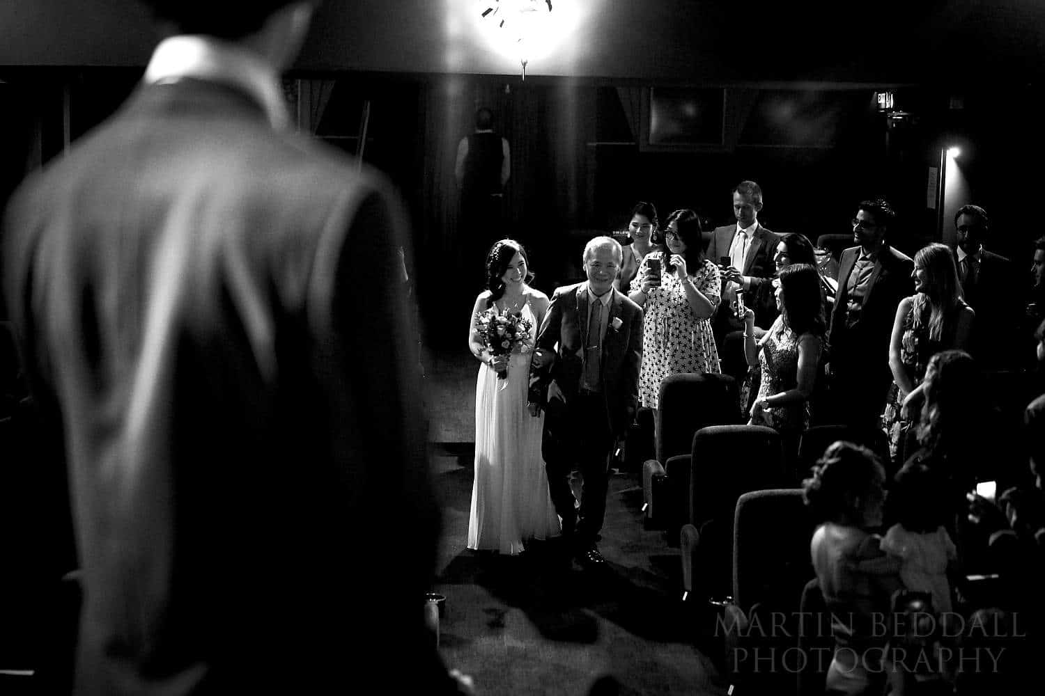 Bride and her father walk down the cinema aisle