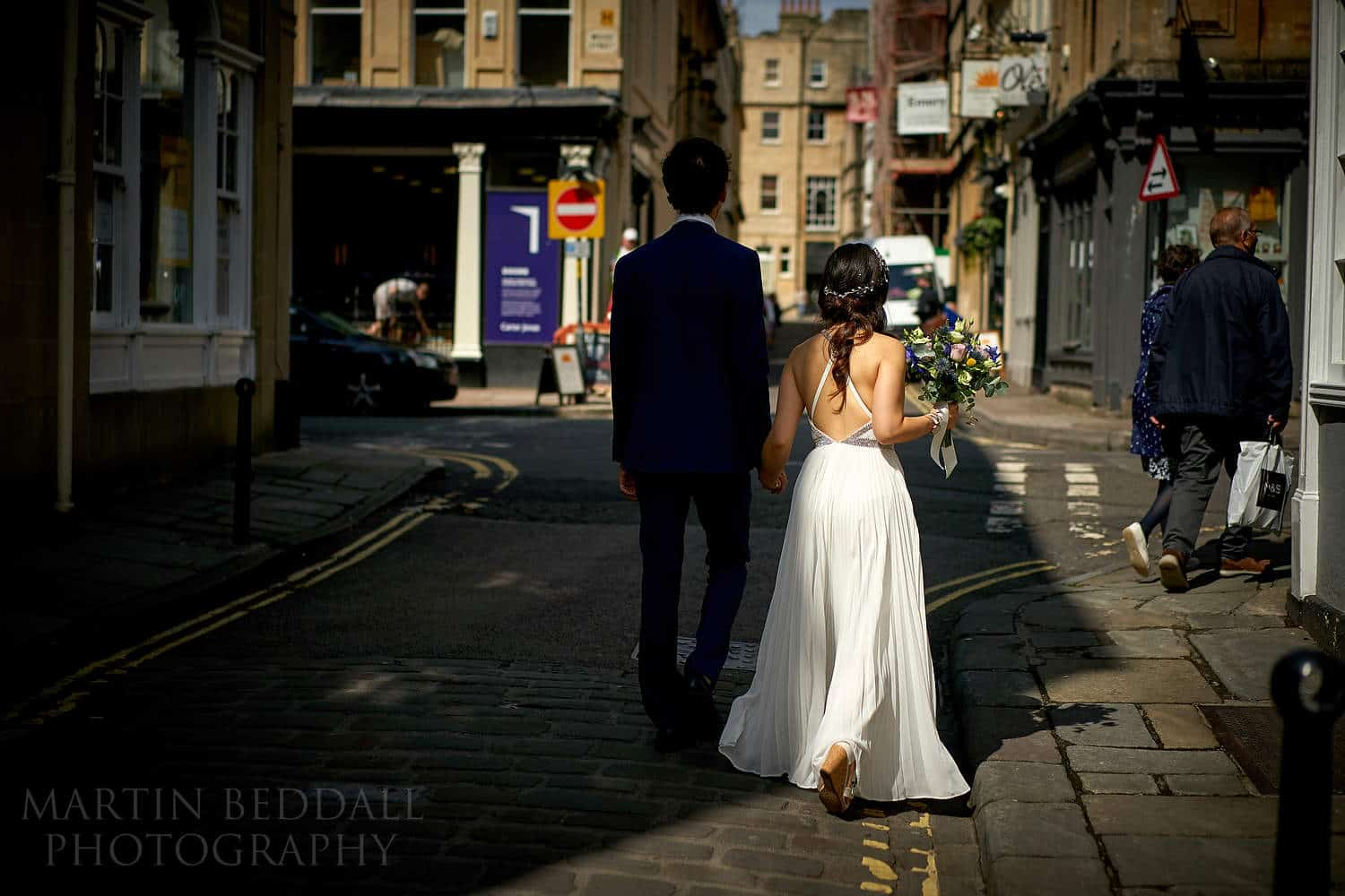 Bride and groom walk through Bath