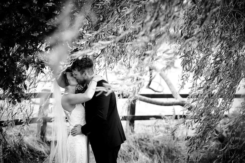 Bride and groom kiss at Oak Barn wedding