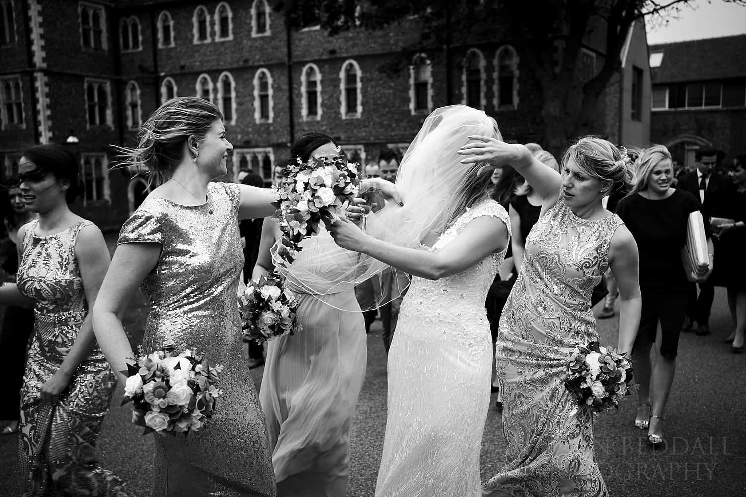 Bridesmaids help with the veil on a windy day