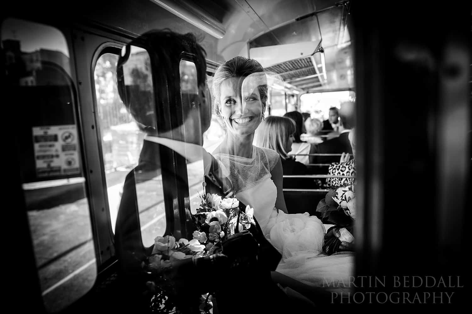 Bride smile at groom sat in wedding bus