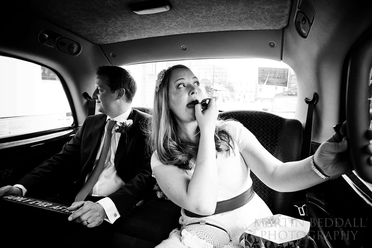 Bride adjusts her makeup in the London taxi