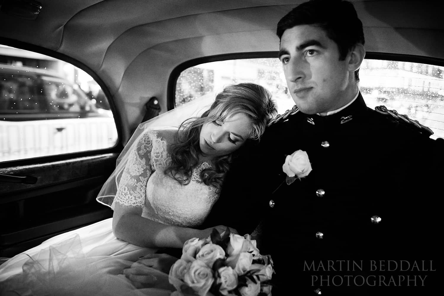 Bride leans her on her husband's shoulfder in the cab